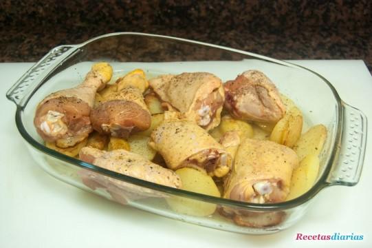 Fuente pollo con patatas antes de meterla en el horno